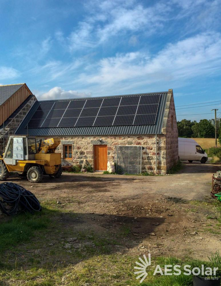 Solar PV on-roof install with yellow digger and white background in background