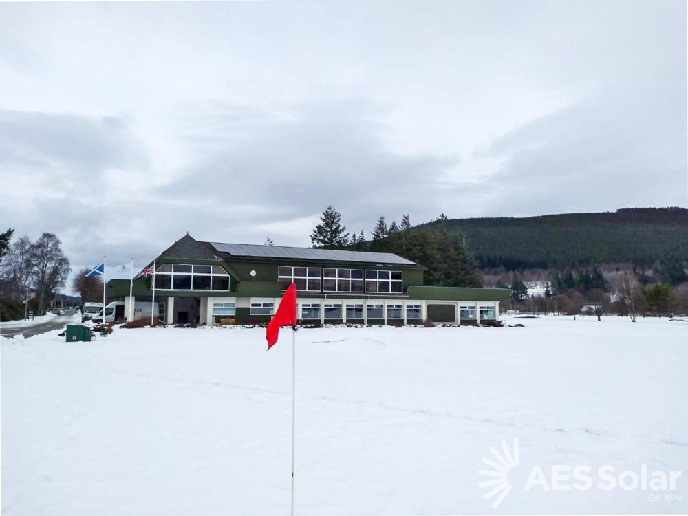 Ballater Golf Club 30kWp PV system pictured in a snowy scene with a red golf flag visible in the foreground