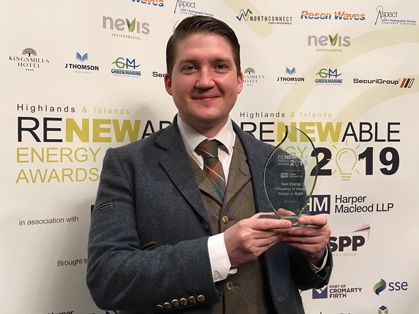 Man holds glass trophy at energy awards