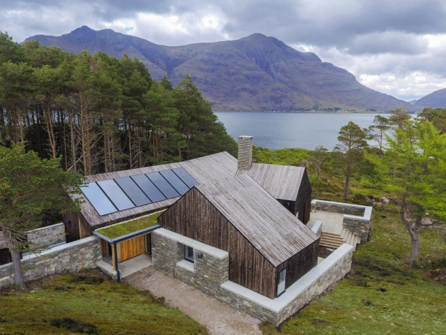 Wooden house with solar panels in a lake side surrounding with mountains and trees