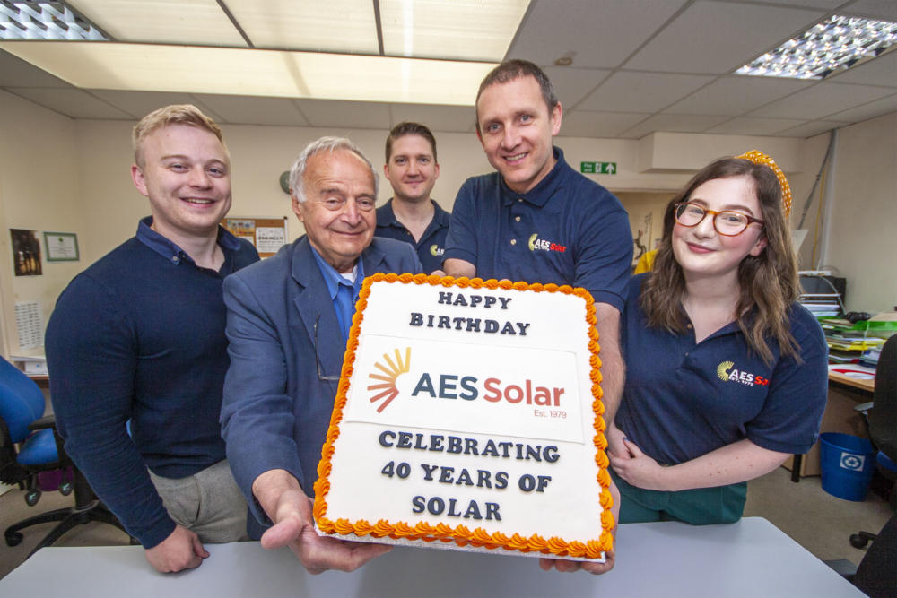 Five members of staff stand around a birthday cake for AES Solar year review