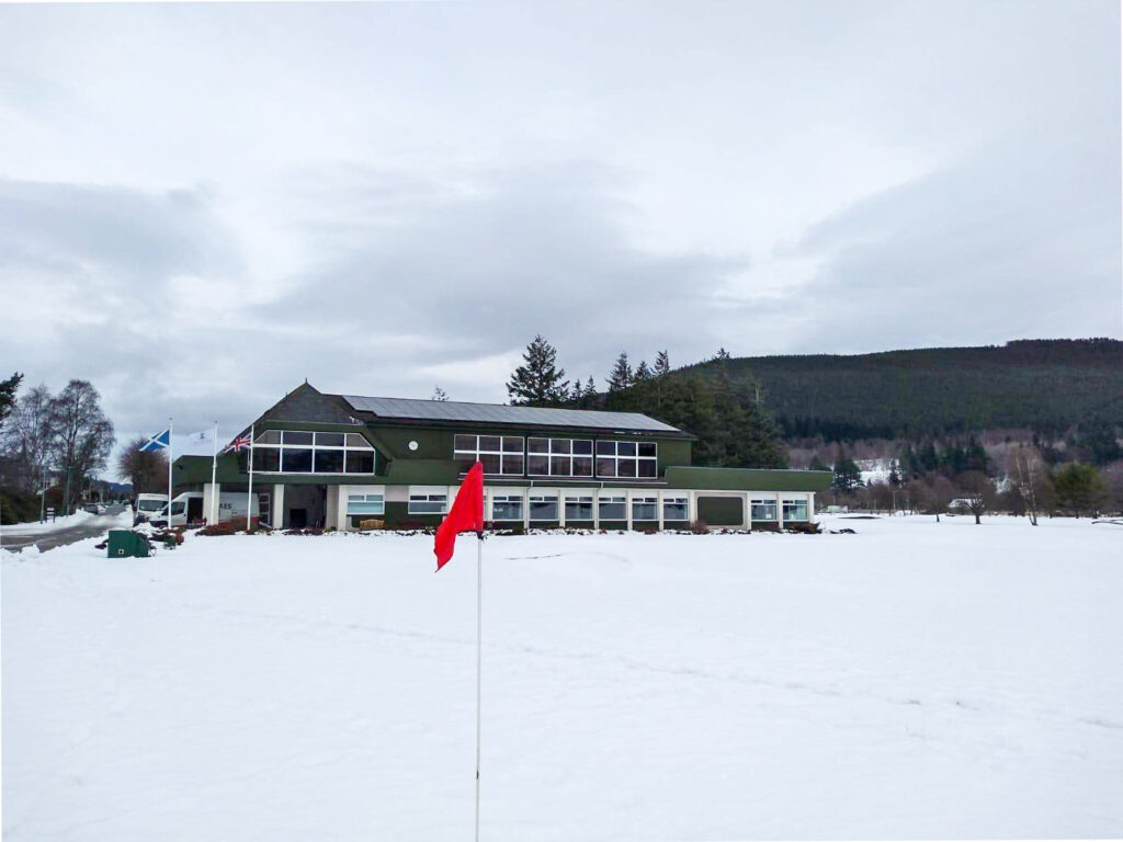 Golf club in a snowy backdrop with red golf flag in foreground