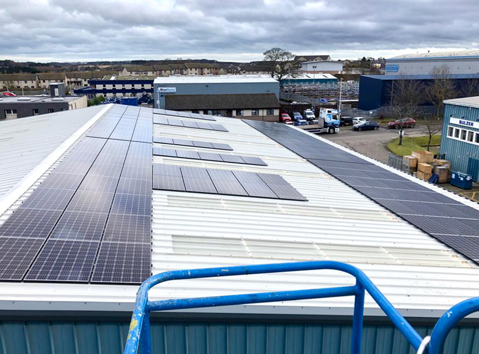 Large corrugated workshop roof with solar panels on roof taken from an aerial work platform