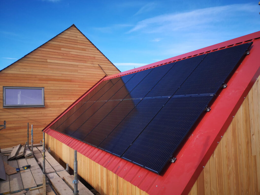 14 black solar panels on a red corrugated roof on a wooden building with blue sky