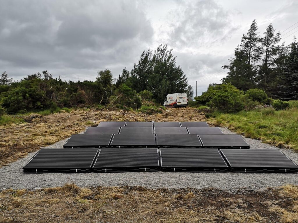 16 solar panels in a cleared wooded area with a white van in the background