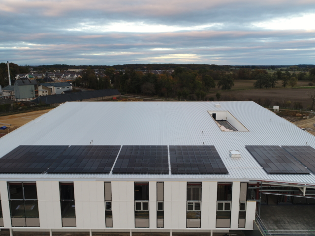 aerial shot of a large building with a large amount of solar panels on the roof