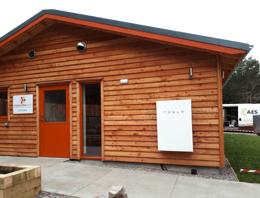 Battery storage installed on the outside of a wooden property