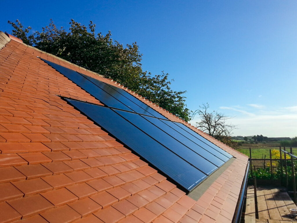 Orange tiled roof with 8 solar panels and blue sky