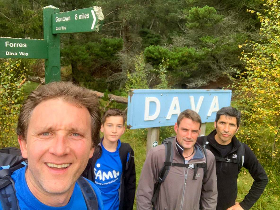 Four men pose for a selfie in front of a walking route signpost