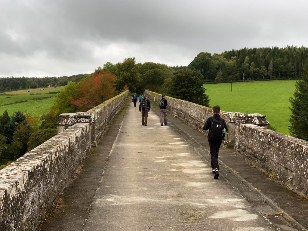 Figures in the distance walk over a large stone bridge