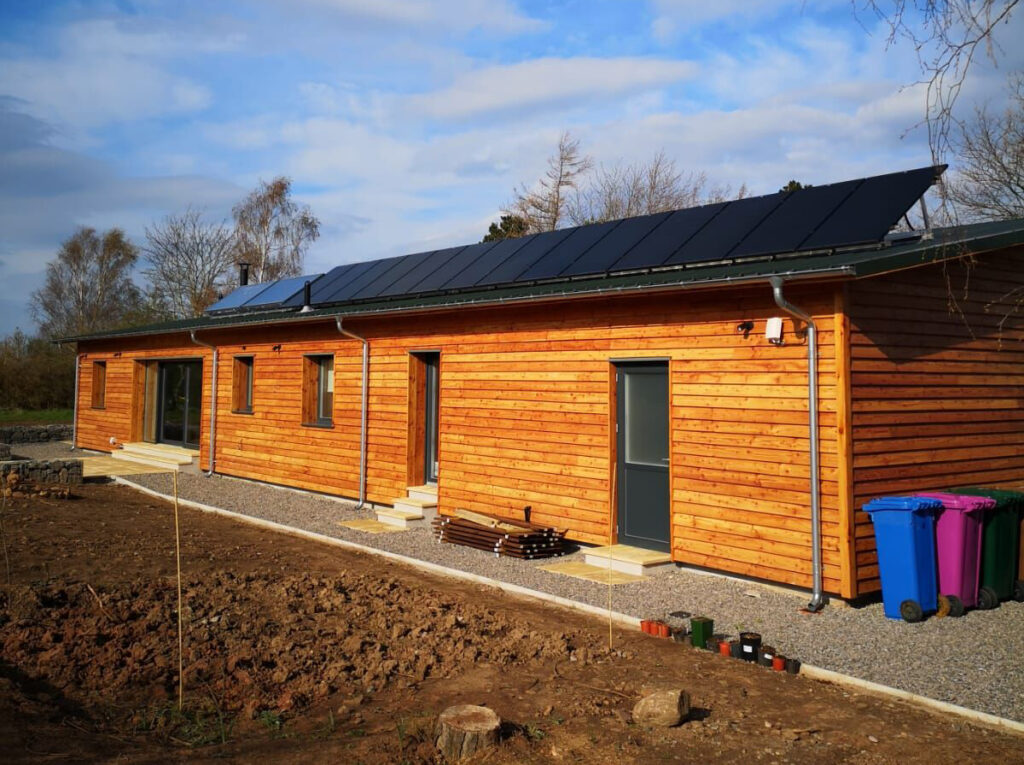 Wooden home of the future with solar panels on roof for AES Solar year review